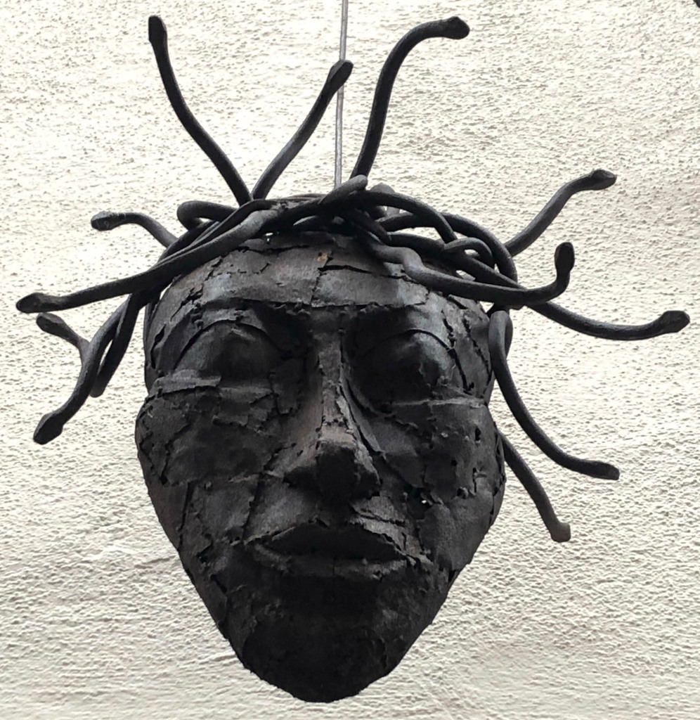Ein schwarzer Kopf mit Schlangen oder Dreadlocks als Haare. Gefunden in Konstanz über einem Friseurladen.